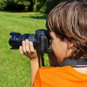 10779379 - kid taking shots with photocamera in park
